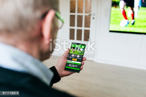 istock Man bets on soccer game with betting app on phone at home 911119374