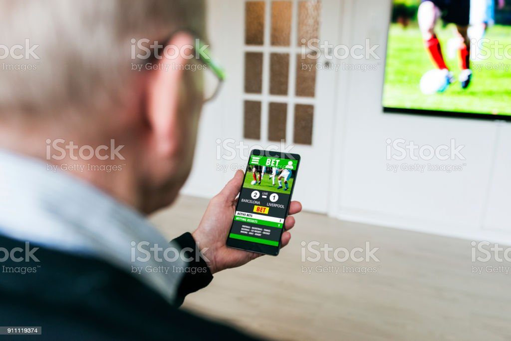 Man bets on soccer game with betting app on phone at home stock photo