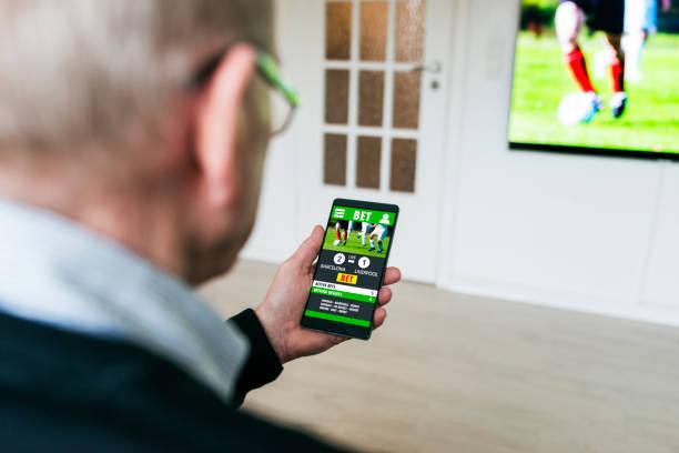 Homme Paris sur le match de football avec app de Paris sur le téléphone à la maison - Photo