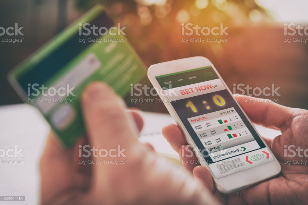 Man betting on sports with smartphone stock photo
