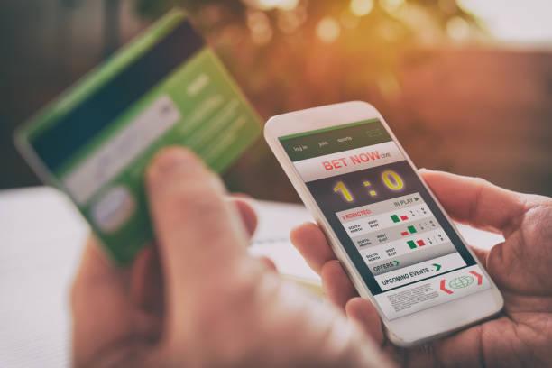 man wedden op sport met smartphone - gaming stockfoto's en -beelden