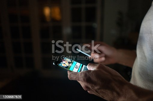 Close-up on a man betting online at home on his cell phone using his credit card. **DESIGN ON SCREEN WAS MADE FROM SCRATCH BY US**