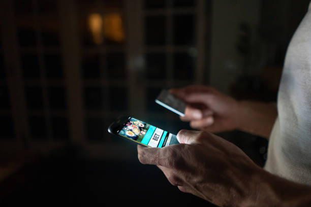 man betting online at home on his cell phone - smartphone addiction not groups stock pictures, royalty-free photos & images