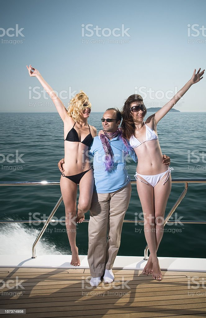 man between two beautiful girls on the yacht stock photo