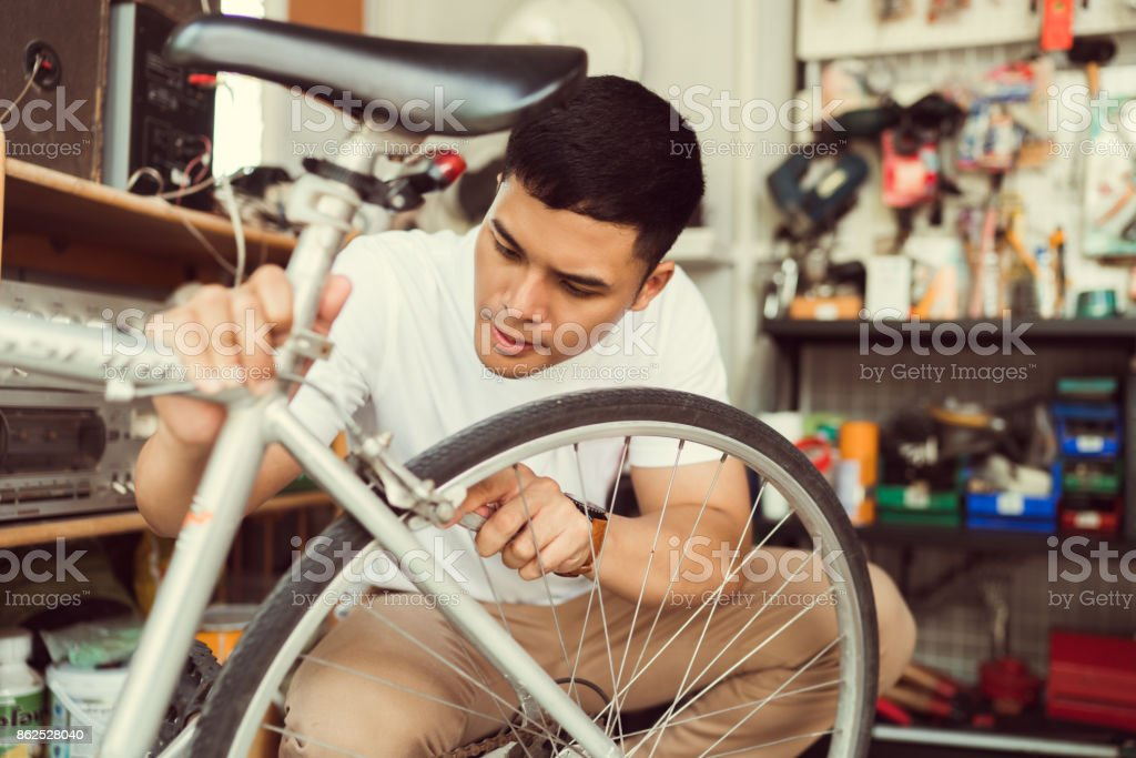 Man bicycle mechanic repairing bicycles stock photo