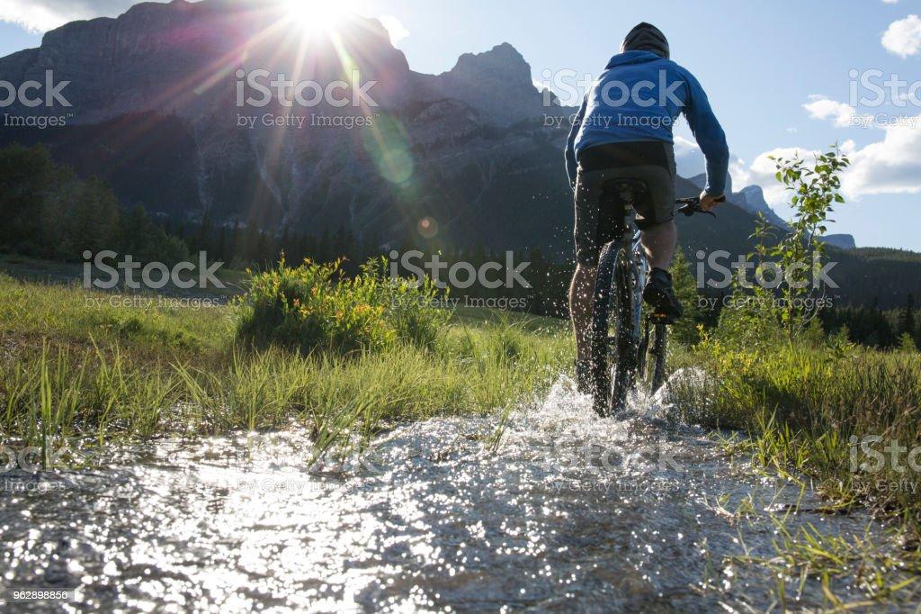 Man bikes upstream in mountain meadow stock photo