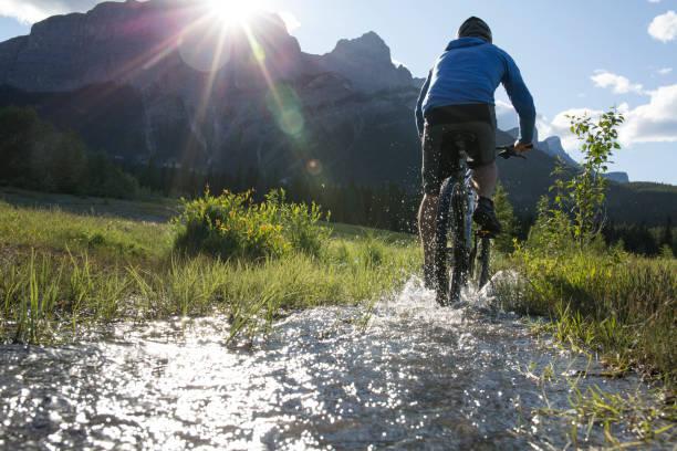 Vélos homme en amont dans la prairie de montagne - Photo