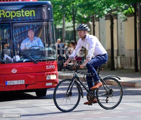 583973114istockphoto Man biking in traffic 822558584