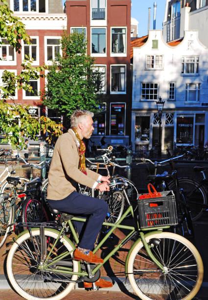 Man Biking to Work dressing elegantly. stock photo