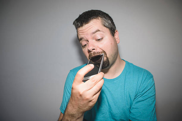man biting and chewing on his smart phone - smartphone addiction not groups stock pictures, royalty-free photos & images