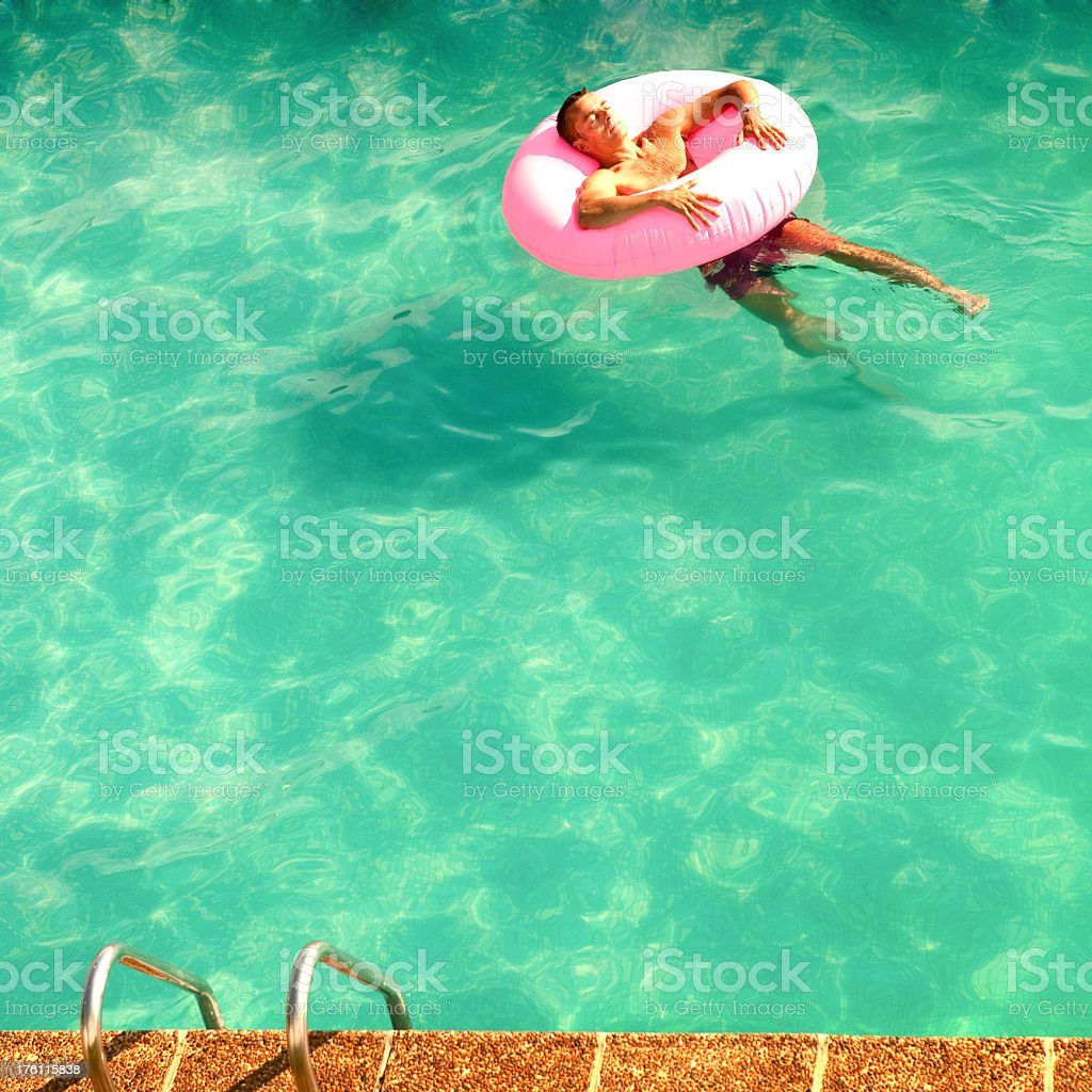 man blissfully relaxed and dreaming in swimming pool on holiday royalty-free stock photo
