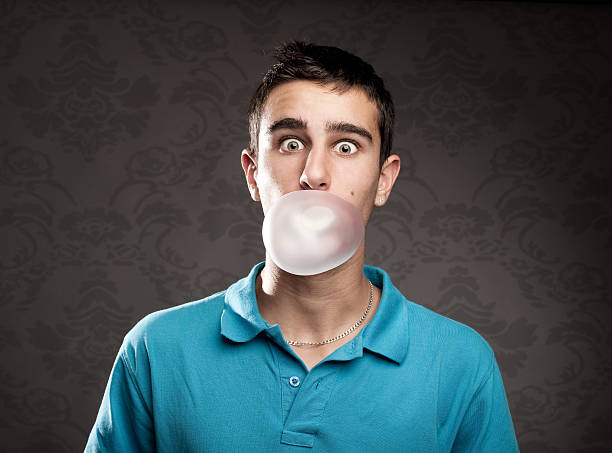 A man blowing a bubble from chewing gum stock photo