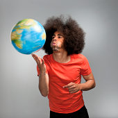 waist up shot of a soccer world cup fan with big afro hair in orange T-shirt blowing at a spinning globe on his fingers on gray background