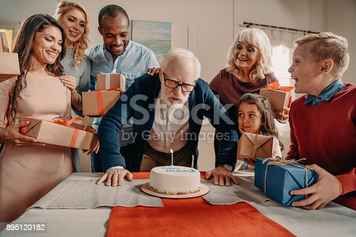 895137896 istock photo man blowing candle on birthday cake 895120182