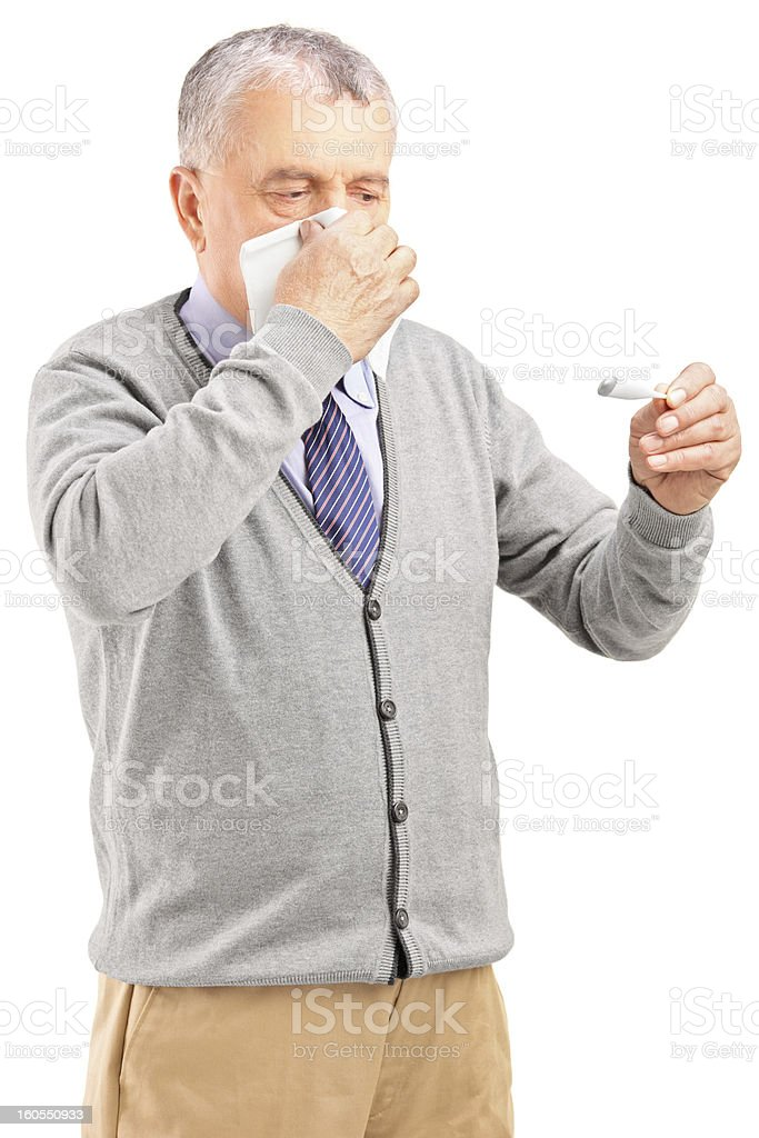 Man blowing his nose and looking at thermometer royalty-free stock photo