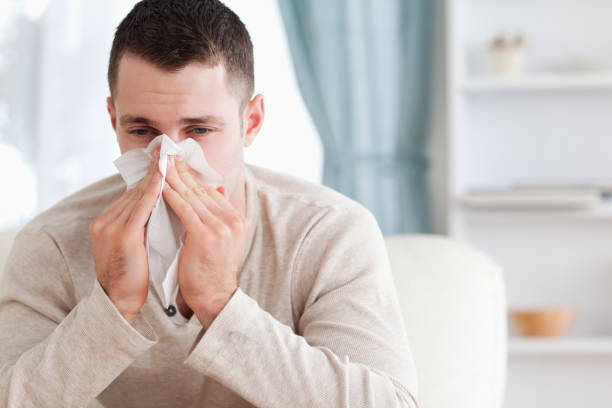Man blowing his nose Man blowing his nose in his living room human parainfluenza virus stock pictures, royalty-free photos & images