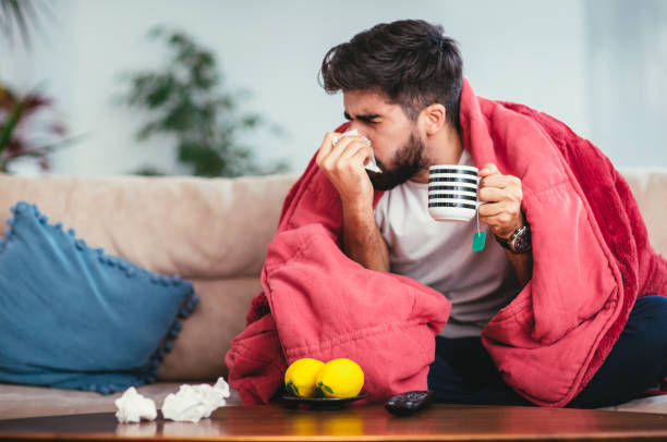 Man blowing his nose while lying sick in bed stock photo