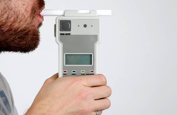 homem soprando em bafômetro - bafometro - fotografias e filmes do acervo