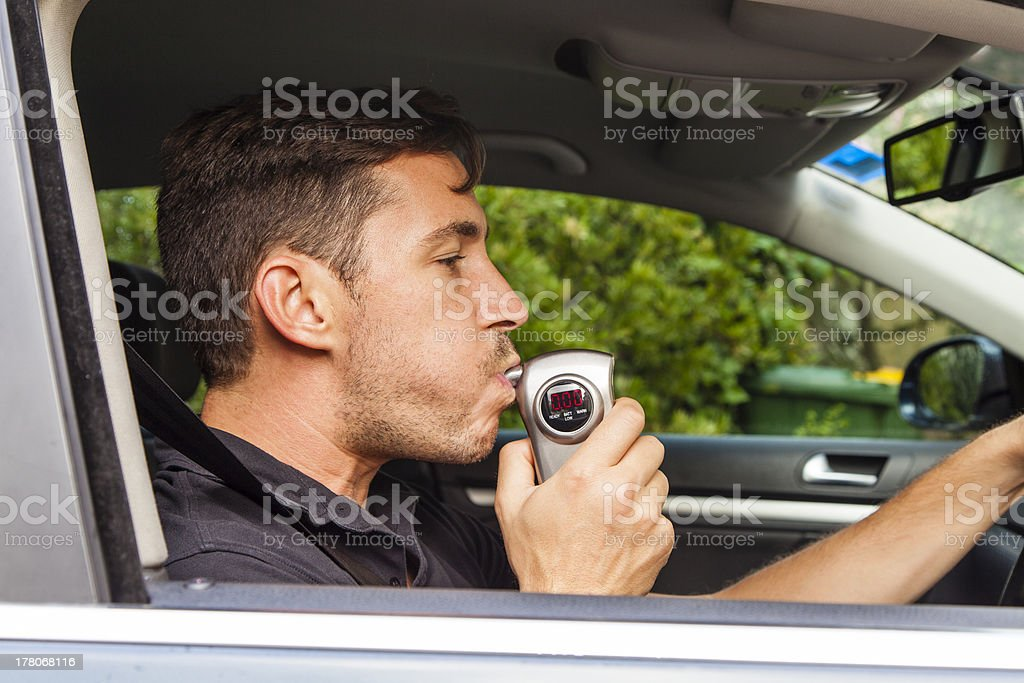 Man blowing into breathalyzer Man in car blowing into breathalyzer Adult Stock Photo