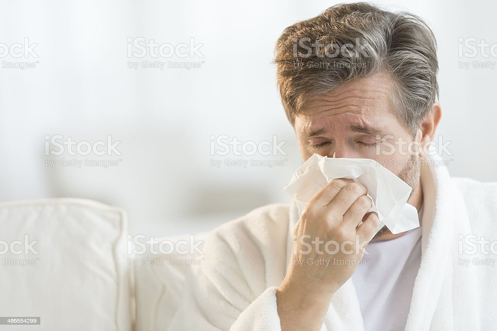 Man Blowing Nose Into Handkerchief stock photo