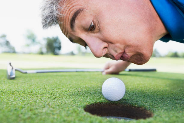 Man blowing on golf ball stock photo