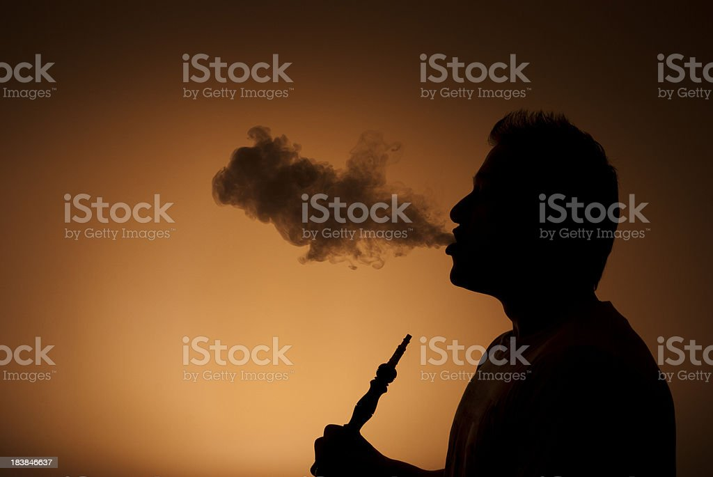 Man blowing water pipe stock photo