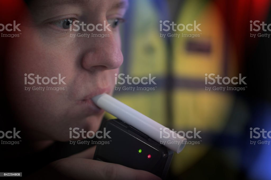 Man Blows in Breathalyser Test to police - Drink Driving - foto de acervo