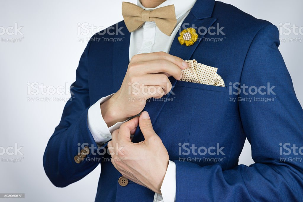 Man in blue suit with coffee cream bowtie color, flower brooch, and...