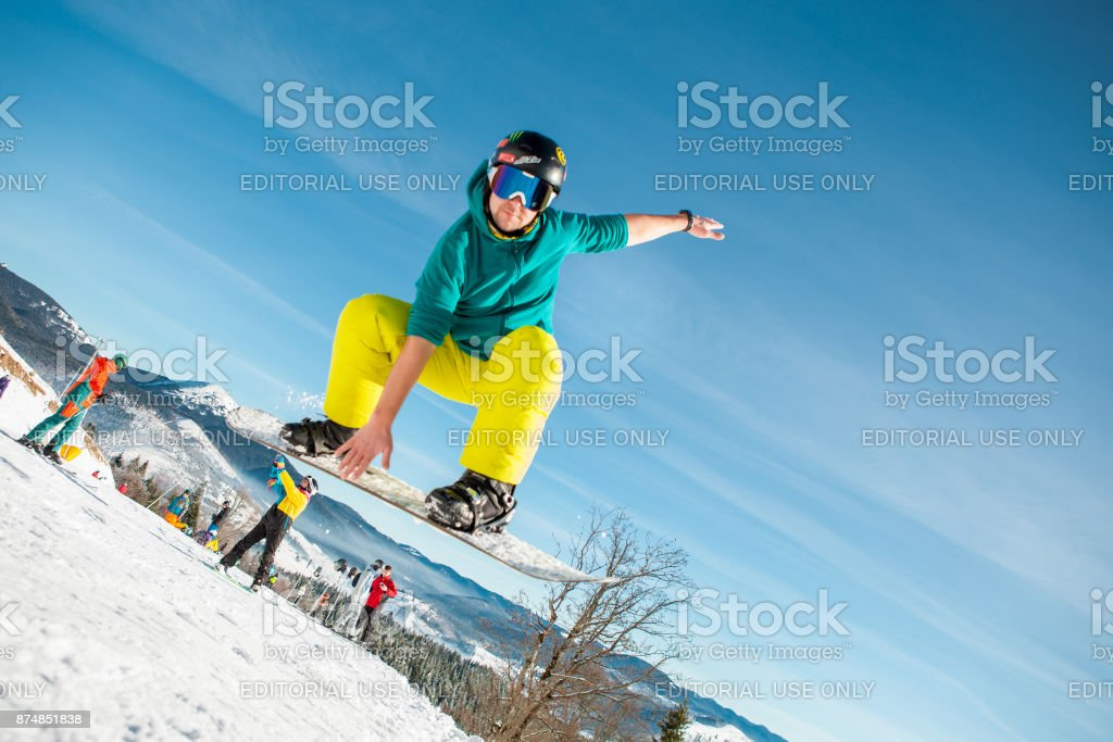 Bukovel, Ukraine - December 22, 2016: Man boarder jumping on his snowboard against the backdrop of mountains, hills and forests in the distance. Bukovel, Carpathian mountains stock photo