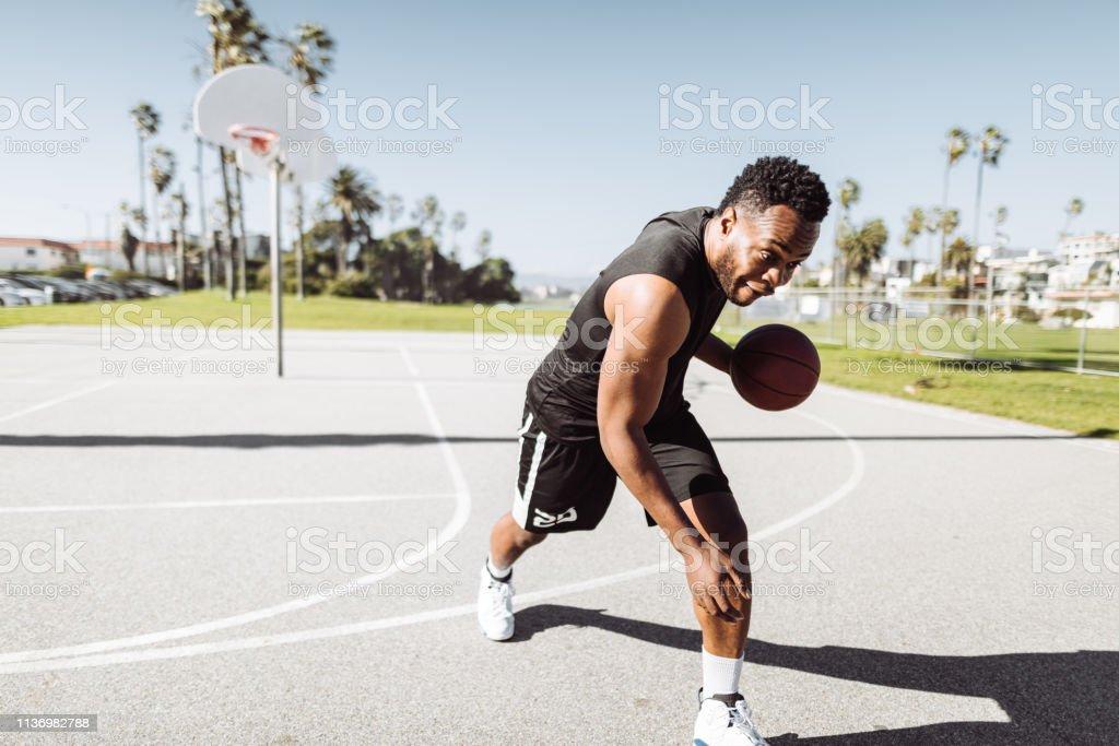 Mann prallt den Ball in einem Straßen-Basketballplatz – Foto