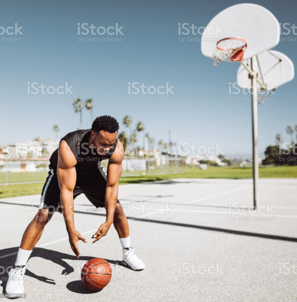 man bouncing the ball in a street basketball court
