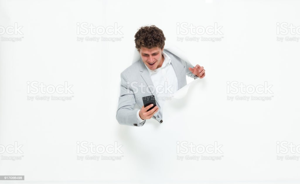 Man break through paper and on phone stock photo