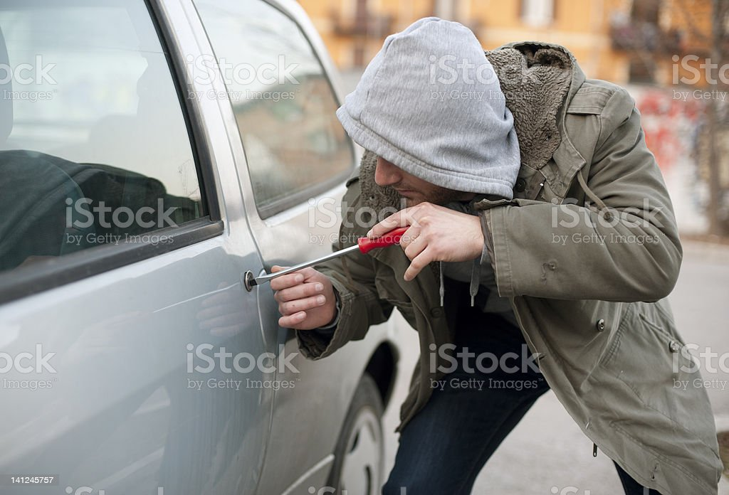A man breaking into a parked car stock photo