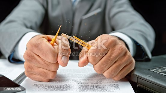 Close-up of businessman breaking pencil.
