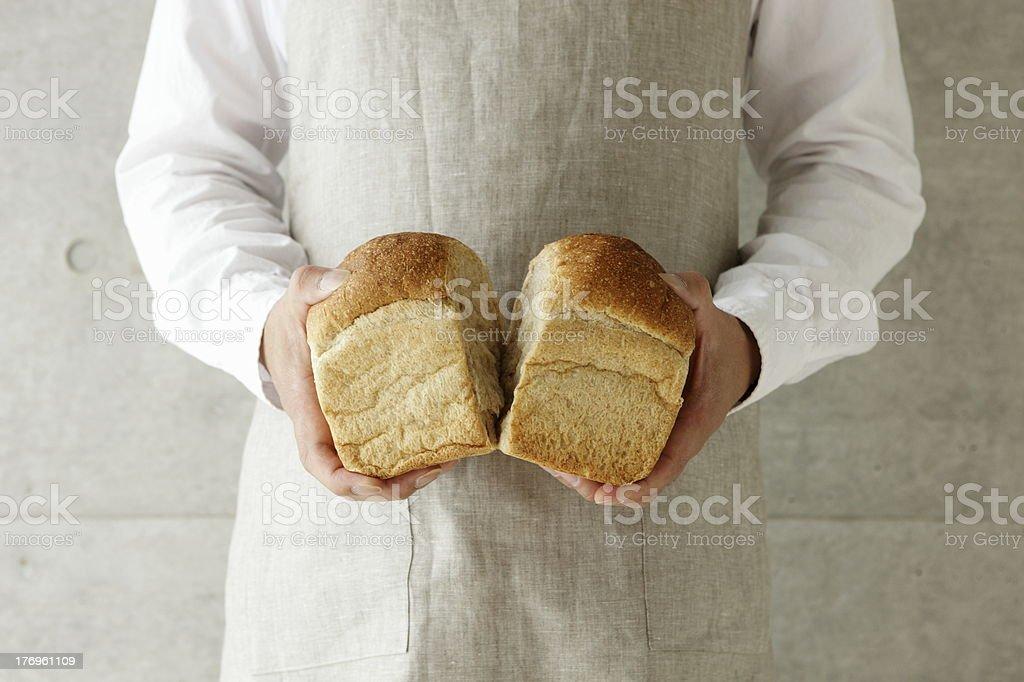 Man breaking piece of bread in half. stock photo