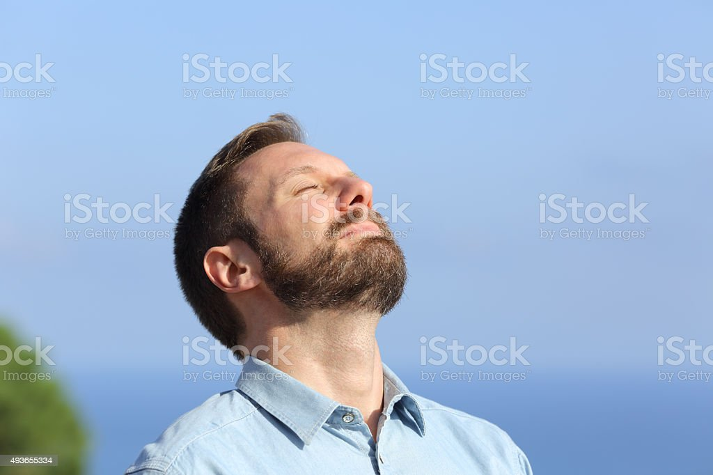 Man breathing deep fresh air outdoors foto