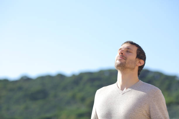 Man breathing fresh air near the mountains stock photo