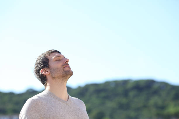 Man breathing outdoors fresh air in the mountains stock photo
