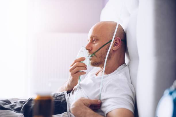 Man breathing through oxygen mask in bed. Covid-19 patient. stock photo