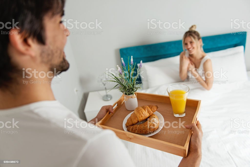 Man bringing breakfast to his girlfriend in bed stock photo