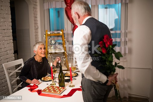 Senior woman smiling when receiving bouquet of roses from her husband