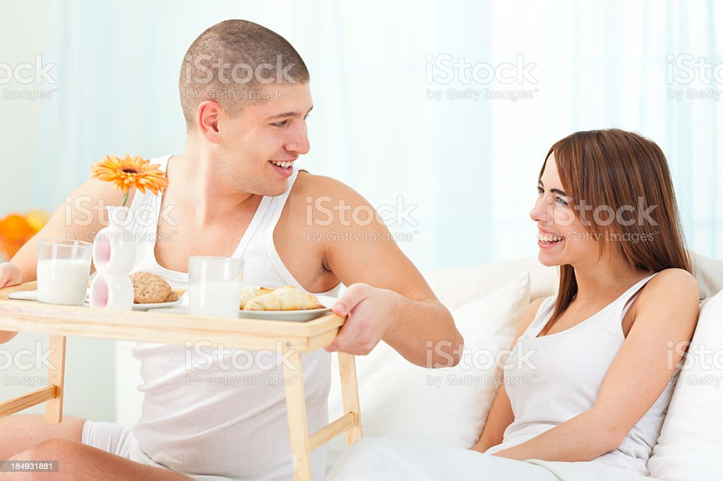 Man brings breakfast to a women in bed royalty-free stock photo