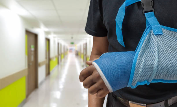 Man broken arm Man broken arm with blurred hospital background plaster stock pictures, royalty-free photos & images