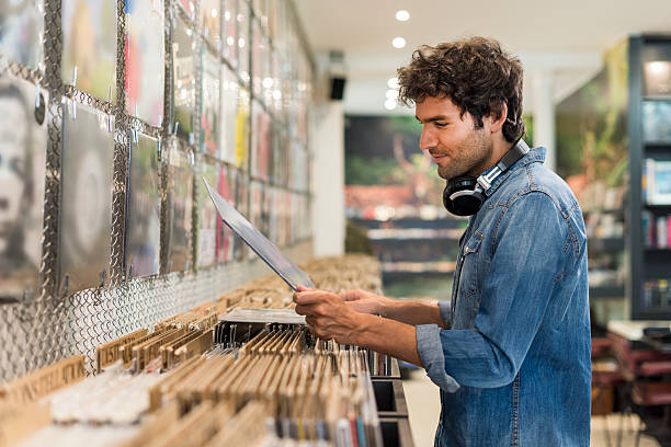 Man browsing vinyl album in a record store stock photo