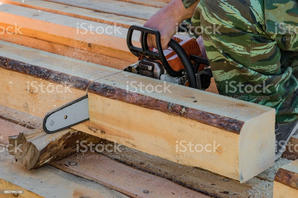 Man, builder, carpenter saws petrol chainsaw new hardwood timber, a building material, stock photo