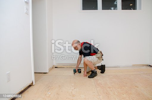 Man building a floor in home basement. He his using drill to screw the plywood