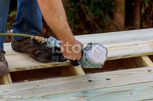 Man building a wooden patio with hammering screwing together beams close up of exterior timber decking.