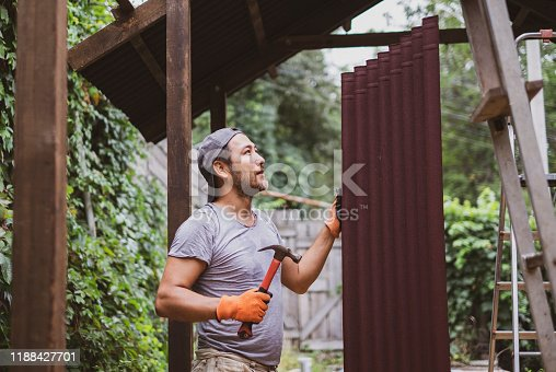 452592895 istock photo Man building roof and holding hammer and roof material onduline. 1188427701
