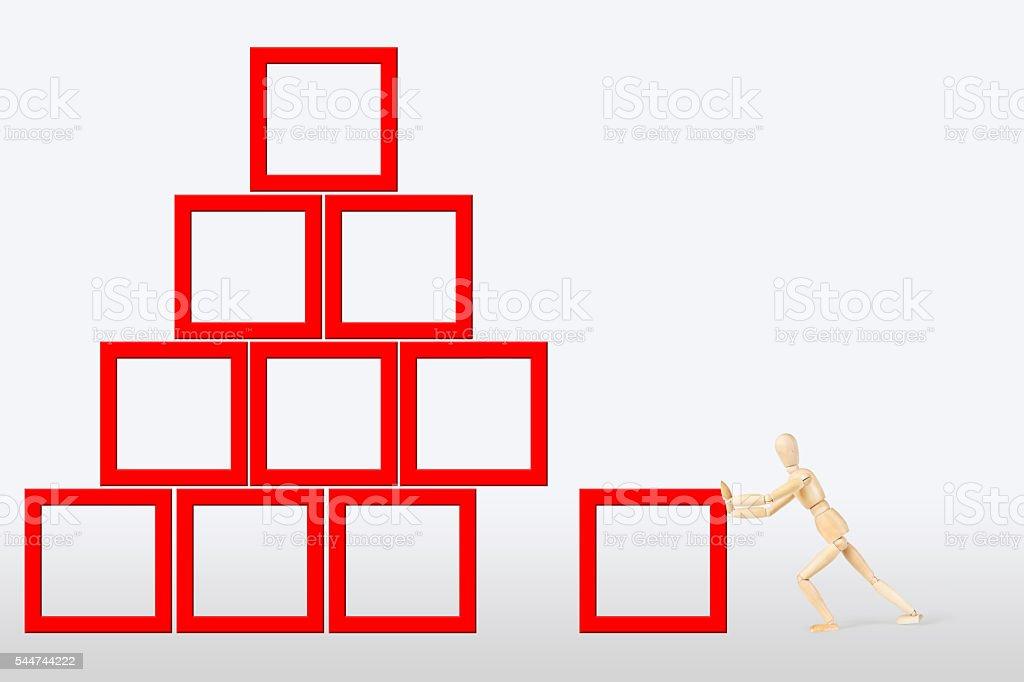 Man builds a construction as a pyramid stock photo