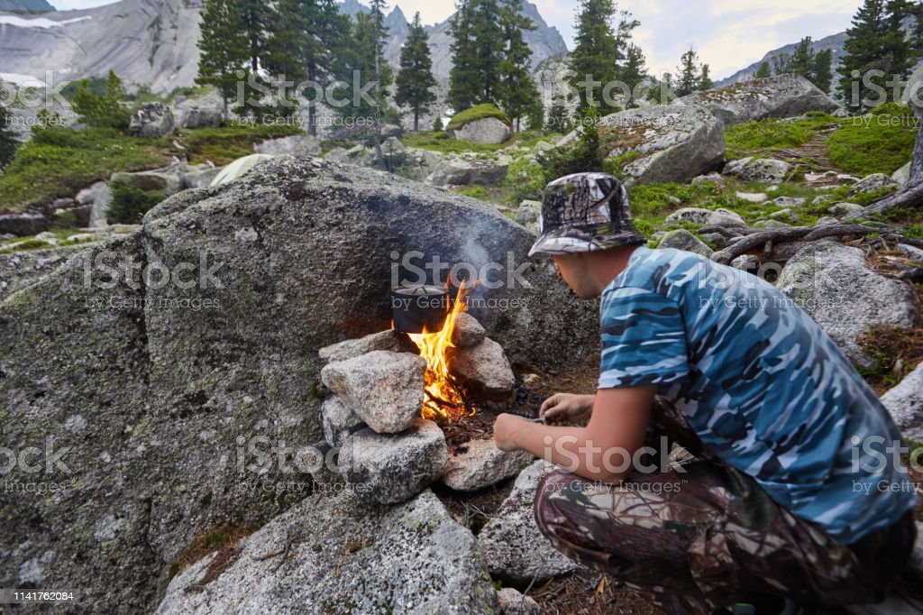 Man built a campfire in the woods in nature. Survive in the mountains...